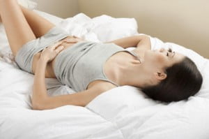 Young woman stroking her belly; bellyache or constipation
